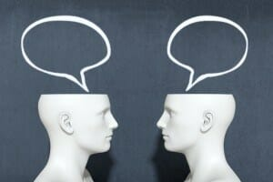 two heads with speech bubbles