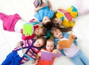 Children lying in a circle reading books